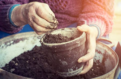 Old woman filling a pot with fresh soil. Symbol of spring Stock Photo