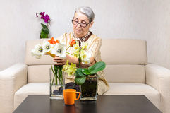 Old woman flowers arrangement Stock Photo