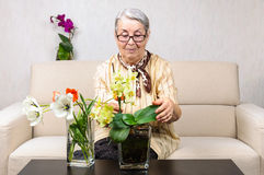 Old woman flowers care Stock Photography