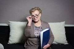 Old woman with a folder holding hands. Old woman in glasses with a folder holding hands Royalty Free Stock Photo