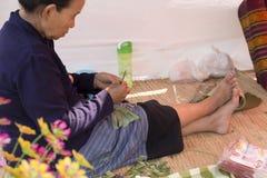 Old woman folding banana leaf Royalty Free Stock Photo