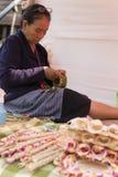 Old woman folding banana leaf Royalty Free Stock Photos