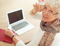 Old Woman in front of Her Laptop Looking at You. Old woman with credit card in front of her laptop looking at you Stock Photo