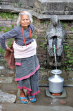 Old woman getting water. The old woman is getting water  in Bhaktapur.Bhaktapur is an ancient Newar town in the east corner of the Kathmandu Valley, Nepal Stock Photography