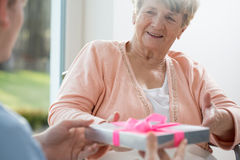 Old woman giving present. Old women giving present her care assistant Stock Images