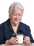 Old woman with glass of milk Royalty Free Stock Photography