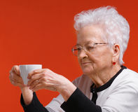 Old woman in glasses enjoying coffee or tea. Cup over orange background royalty free stock photo