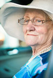 Old woman in glasses and a hat sitting in the car Stock Photography