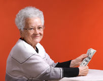 Old woman in glasses holding money Royalty Free Stock Image