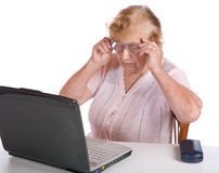 The old woman in glasses looks at  notebook Stock Photography