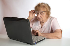 The old woman in glasses looks at the  notebook Stock Photo