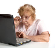 The old woman in glasses looks at the  notebook Stock Image