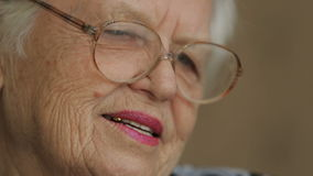 Old woman in a glasses. Old woman reading book at home stock video footage