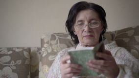 Old woman in glasses reading a prayer book on a sofa.  stock video