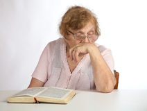 Old woman in glasses reads Royalty Free Stock Image