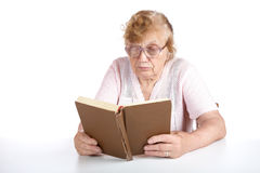 Old woman in glasses reads the book Royalty Free Stock Photos