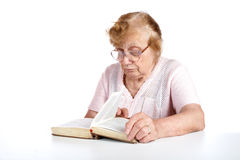 Old woman in glasses reads the book Royalty Free Stock Image