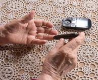 Old woman with glucometer checking blood sugar level Royalty Free Stock Photos