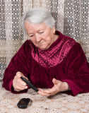 Old woman with glucometer checking blood sugar level. At home royalty free stock image