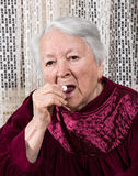 Old woman going to take the medicine Stock Image