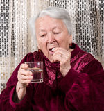 Old woman going to take the medicine. At home Stock Photography