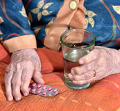 Old woman going to take pills. Old woman going to take the medicine at home Royalty Free Stock Photos