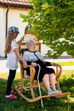 Old woman with granddaughter in the garden. Old women with granddaughter in the garden. Enjoying summer time Stock Photos
