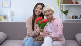 Old woman with granddaughter holding bunch of tulips and looking at camera. Stock footage stock video footage