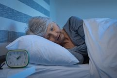 Senior woman sleeping. Old woman in grey hair sleeping peacefully at night time in bed. Senior woman lying on side and sleeping at home. Mature woman feeling royalty free stock photos