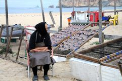 Old woman guards stock fish