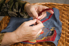 Old woman hand. Embroiders with a needle and a thread Royalty Free Stock Image