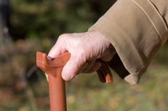 Old woman hand leans on walking stick Royalty Free Stock Images