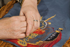 Old woman hand with a needle and a thread Royalty Free Stock Photo