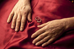 Old woman hands. Isolated on red, with 2 rings behind Stock Photo