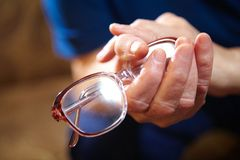 Old woman hands with eyeglasses Royalty Free Stock Photo