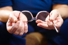 Old woman hands with eyeglasses Royalty Free Stock Photography