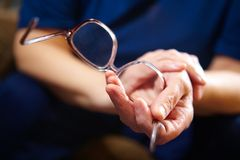 Old woman hands with eyeglasses Stock Photography
