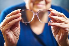 Old woman hands with eyeglasses Stock Image