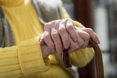 Old woman hands holding a cane Royalty Free Stock Photo