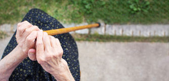 Old woman hands holding a walking cane. Outdoors royalty free stock image