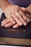 Old woman hands on Holy Bible Stock Photography