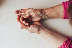 Old woman hands on table top view space for text. Close-up shot of a senior woman& x27;s hands resting on light background. Old lady sitting with her hands stock image