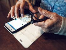 Old woman hands using mobile device Stock Photography
