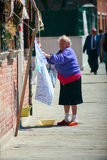 Old woman hanging laundry Royalty Free Stock Photography