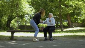 Old woman has a heart attack in park and ask help in young woman. Old woman with heart attack sit on the bench in park and asks help in passersby. Young girl not stock video