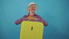 Old woman in a hat winks and with a suitcase in her hand prepares to leave on a blue background. Positive happy senior woman in a hat and winks with a suitcase stock video footage
