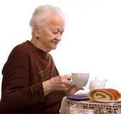 Old woman having breakfast Stock Photo