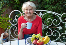 Old Woman Having a Coffee at the Garden Stock Images