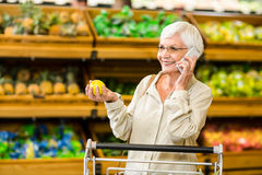 Old woman having a phone call while holding an apple Stock Images