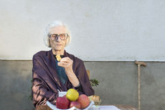 Old woman having a snack in the backyard royalty free stock photos